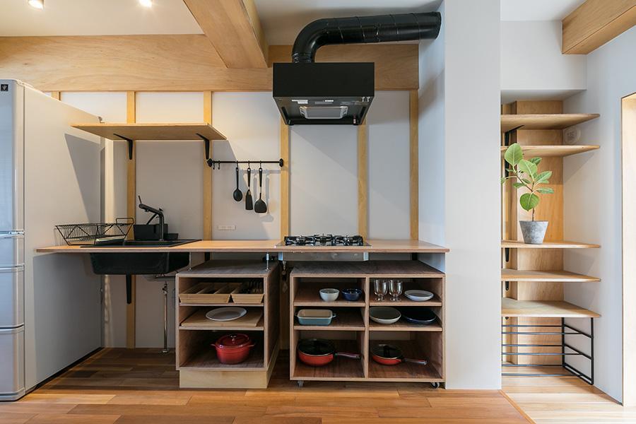 料理好きな平岡さんの希望を反映し、使い勝手よく造作したキッチン。シンクやカラン、コンロ、レンジフードは黒で統一した。「ダクトは黒いものがなかったので、自分たちで黒く塗りました」と原﨑さん。
