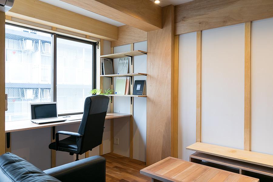 窓際に設けた仕事スペース。棚には内装のカタログなどが並ぶ。「慣れ親しんだ街並みを眺めながら作業できるところが気に入っています」と平岡さん。