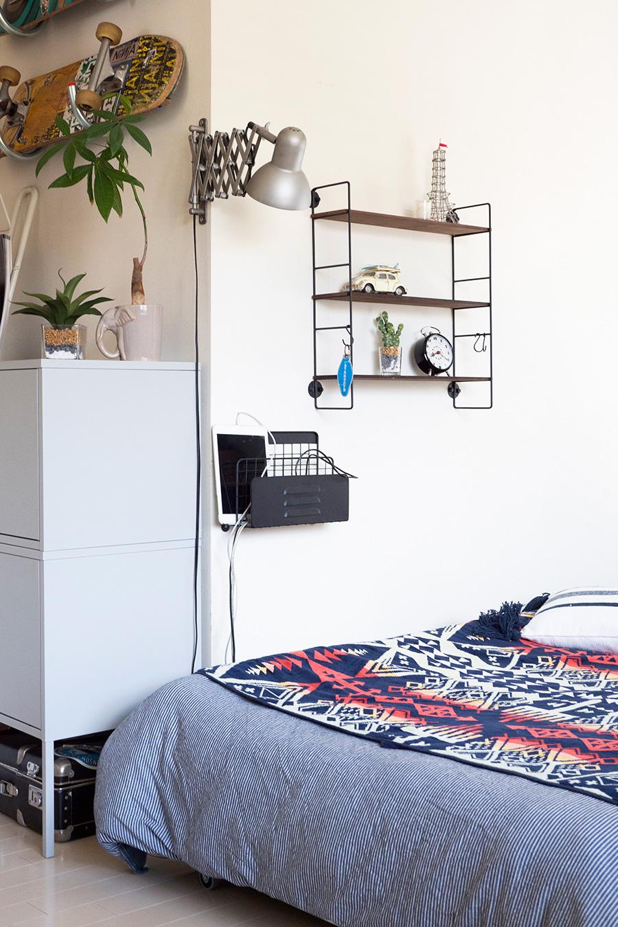 ベッド脇の壁に電子機器置き場を設置。あちこちに散らばるのを防いでいる。