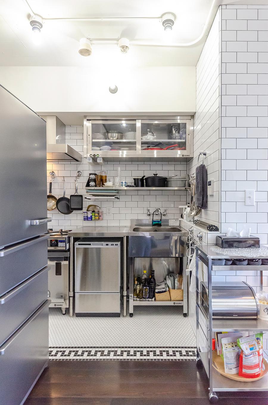 白いタイルがキッチンとリビングの領域を仕切っている。