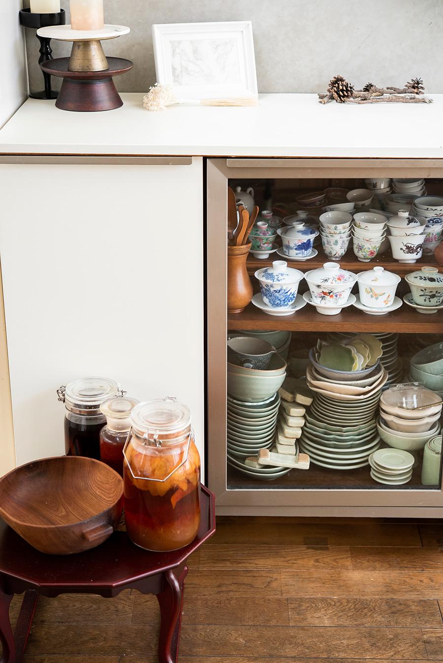 ベトナムのバッチャン焼きなど、キャビネットにはアジアの陶器がひしめく。左手前はお手製のプラム酢。ジュースにしたり、お料理に使ったり。
