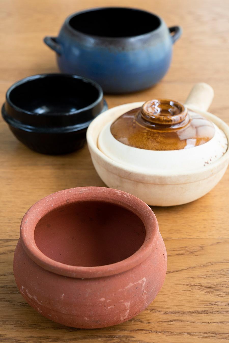 (手前から)トムヤムクン用の素焼きの鍋は、野菜を盛りつけたりしてもかわいい。持ち手の付いたベトナムの鍋は、麻婆豆腐など一人分ずつサーブするのに便利。羽釜風の土鍋は韓国のもの。いちばん奥の青い鍋は、台湾のオーガニックマーケットで見つけた作家もの。