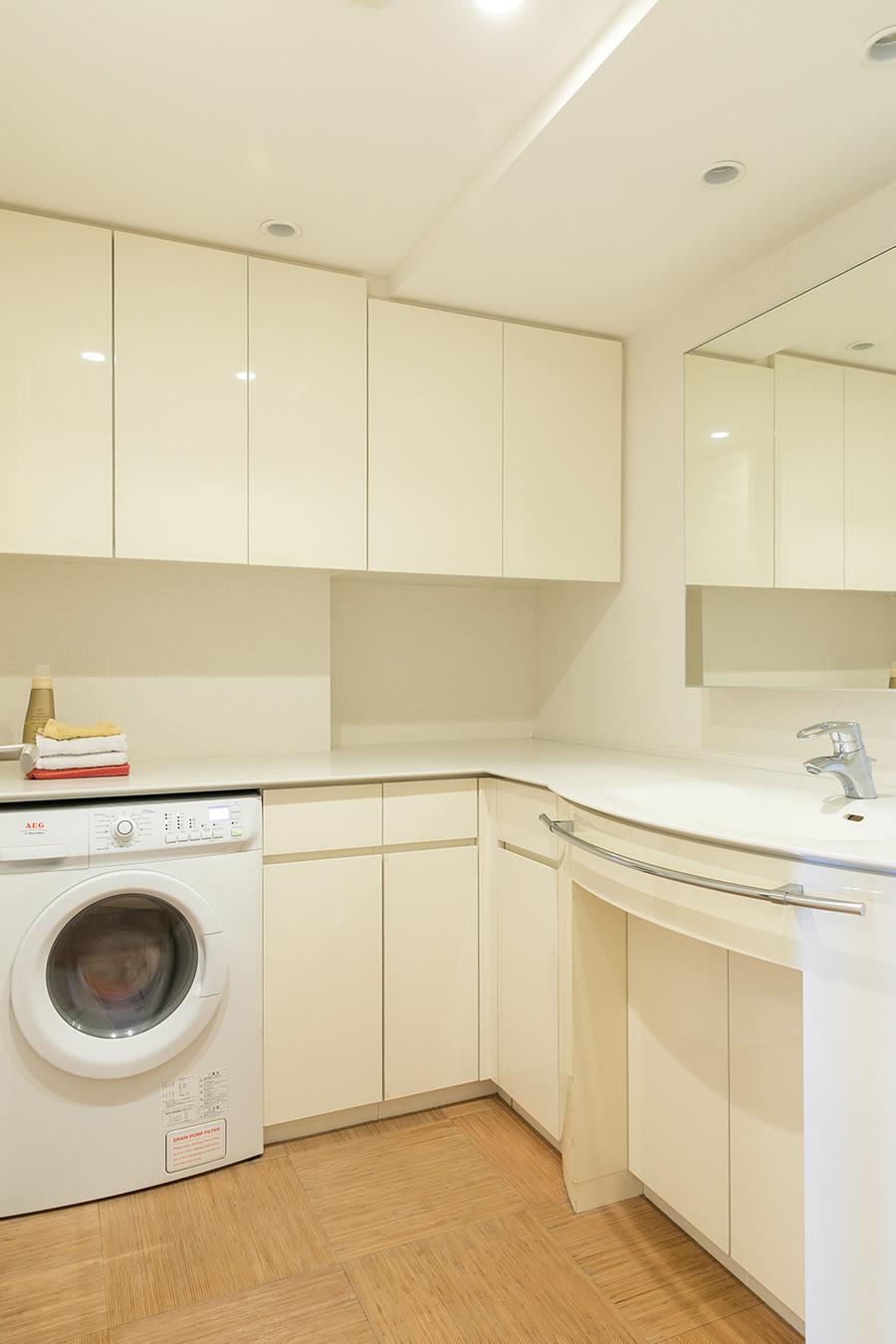 AEG製のビルトイン洗濯機を据えたホテルライクな設えの洗面所。