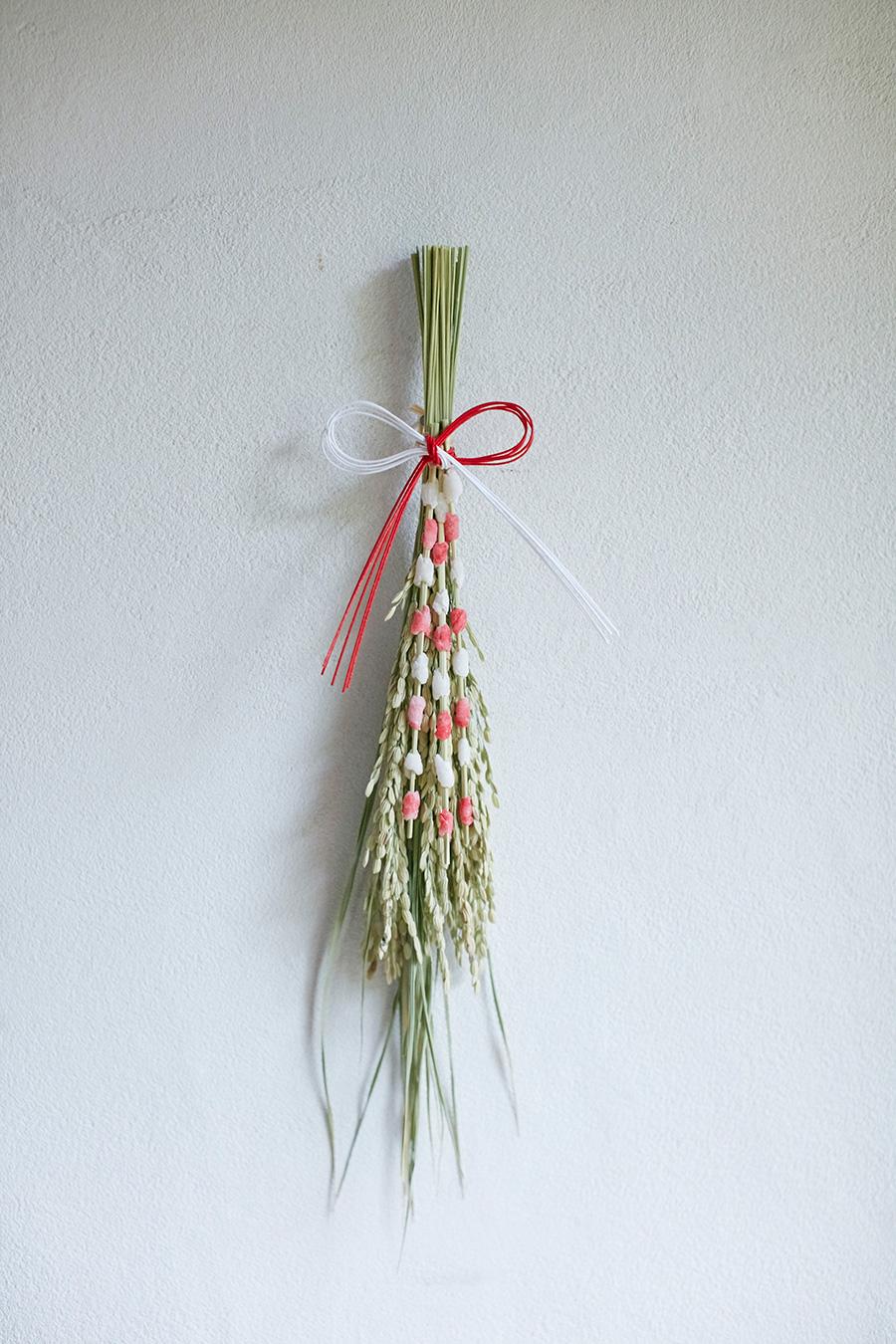 稲穂と餅花を束ね、水引を結んで飾る。