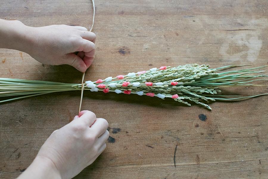 葉の上に稲穂、餅花を重ねて束ね、ラフィアできつく縛る。ラフィアは軽く湿らせてから使うと切れにくい。