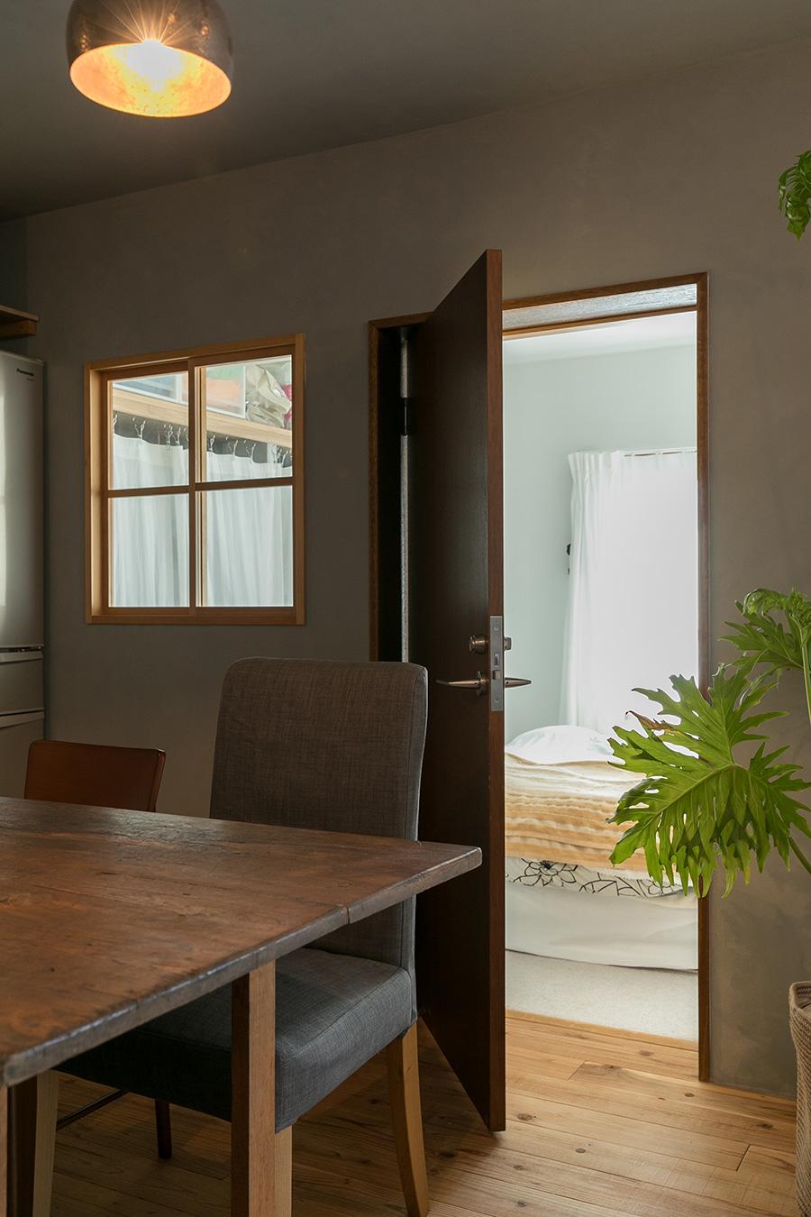 ドアの向こうが、2面採光の明るく気持ちのいい寝室。寝室とダイニングの間に、田の字の正方形の窓を作った。