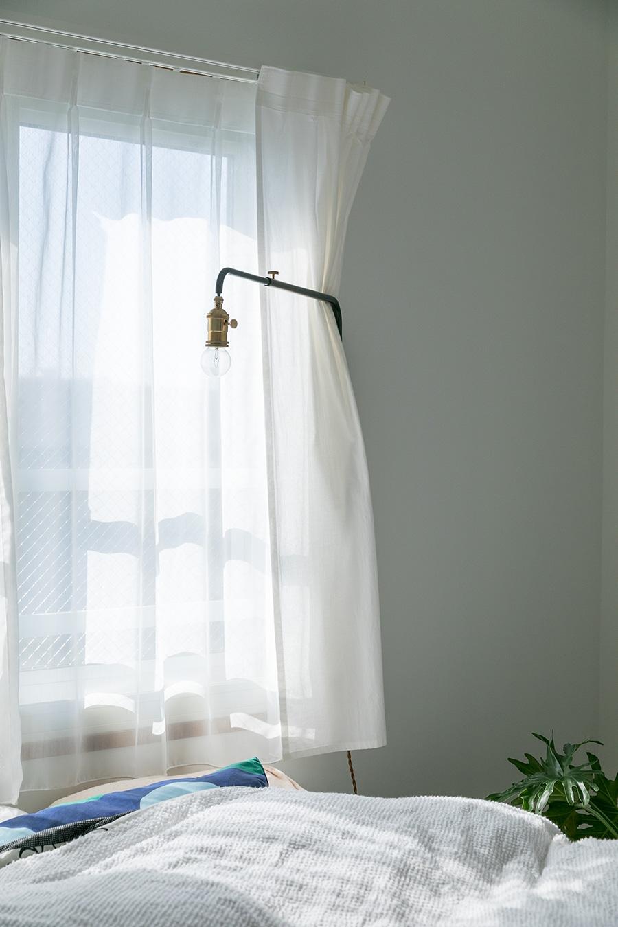 カーテンのドレープ越しのやわらかな光が心地よい寝室。