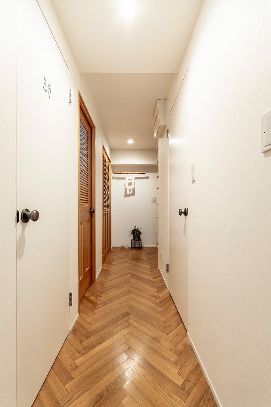 ヘリンボーン張りの廊下。ドアはすべて付け替え、ドアノブもセレクト。