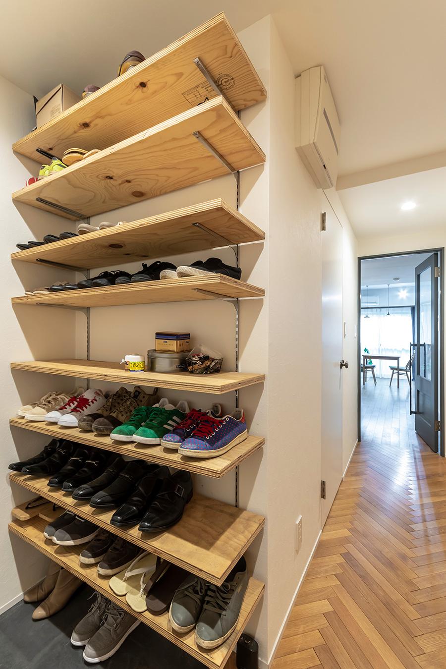 靴の収納はオープンな棚に。玄関の床はモルタルに墨を混ぜて着色した。