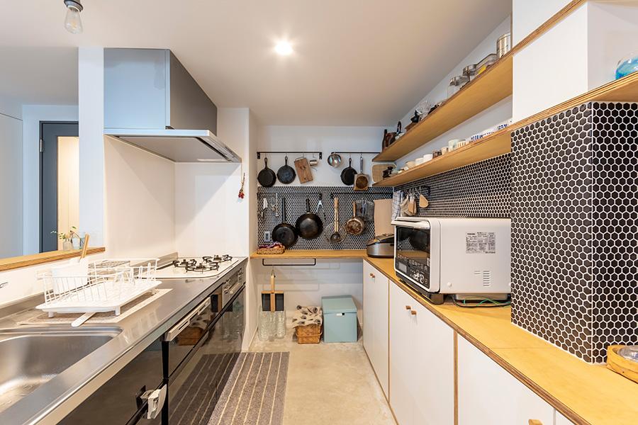 油ハネなどを考えて半分のみ壁を設けたキッチン。使いやすいシステムキッチンを取り入れつつ、見える部分は美しくディスプレイ。