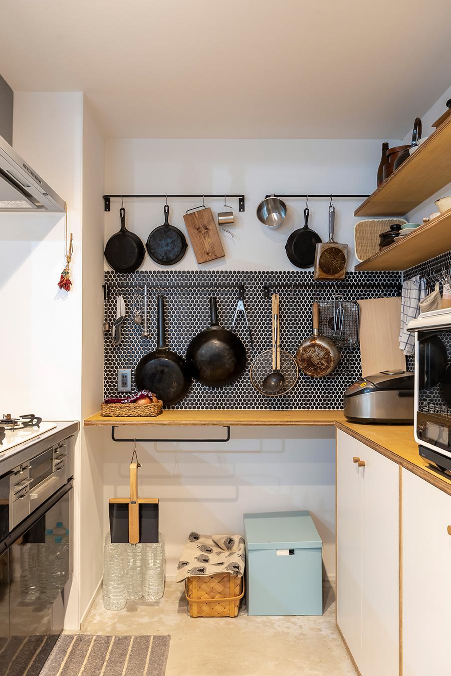 6角形のタイルを部分的にあしらい、キッチンツールを吊るして収納。すぐに手に取ることができて便利。調理器具は夫の愛用品。