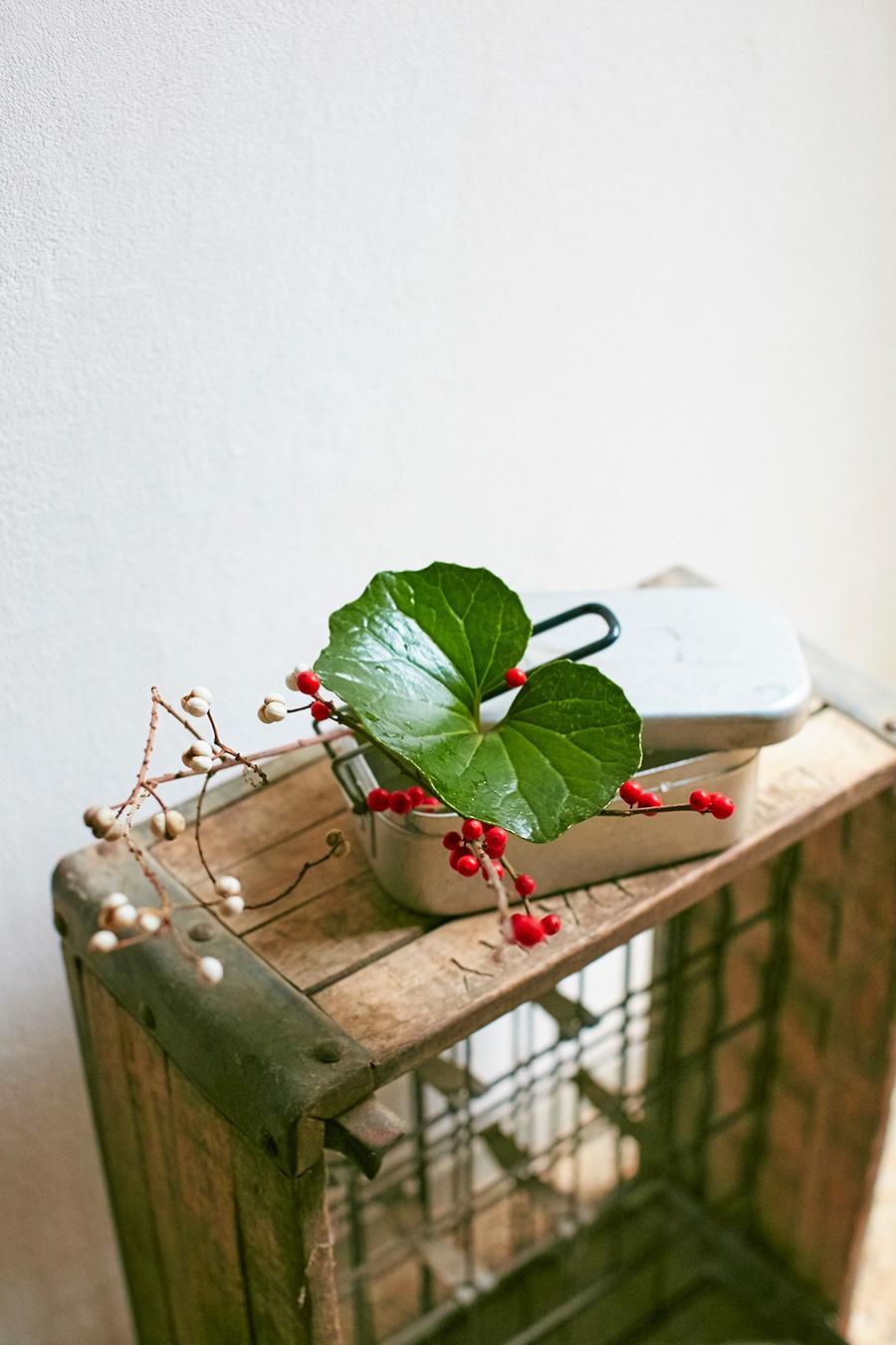 キャンプで使う飯盒に、赤のウメモドキ、白のナンキンハゼ、緑のツワブキの葉を合わせた。「木の実だけを使うときは、葉を花に見立てて飾ります。脇役に回ることが多かった葉が主役になることで、また違った見え方を楽しめます」
