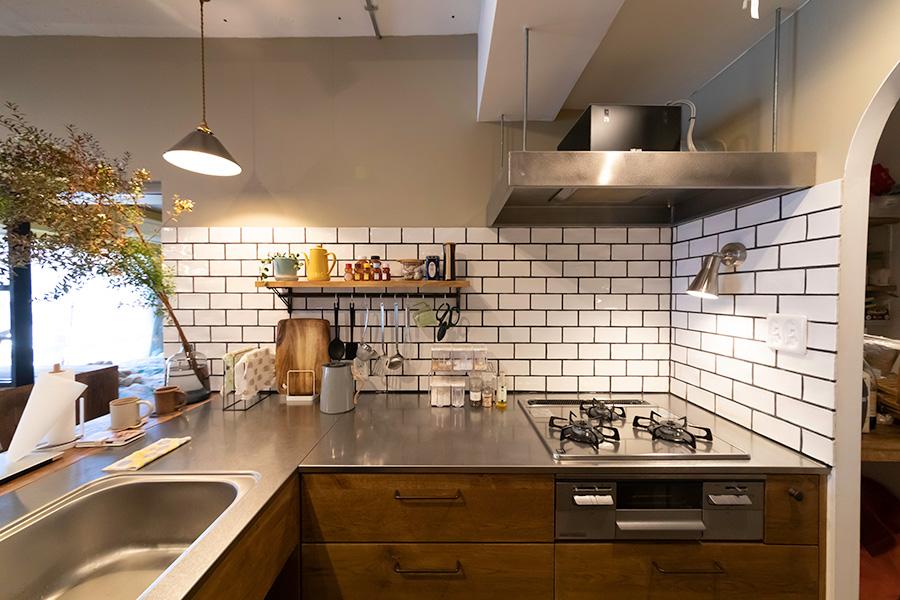 キッチンはL字型。白いタイルを黒の目地で締めた。
