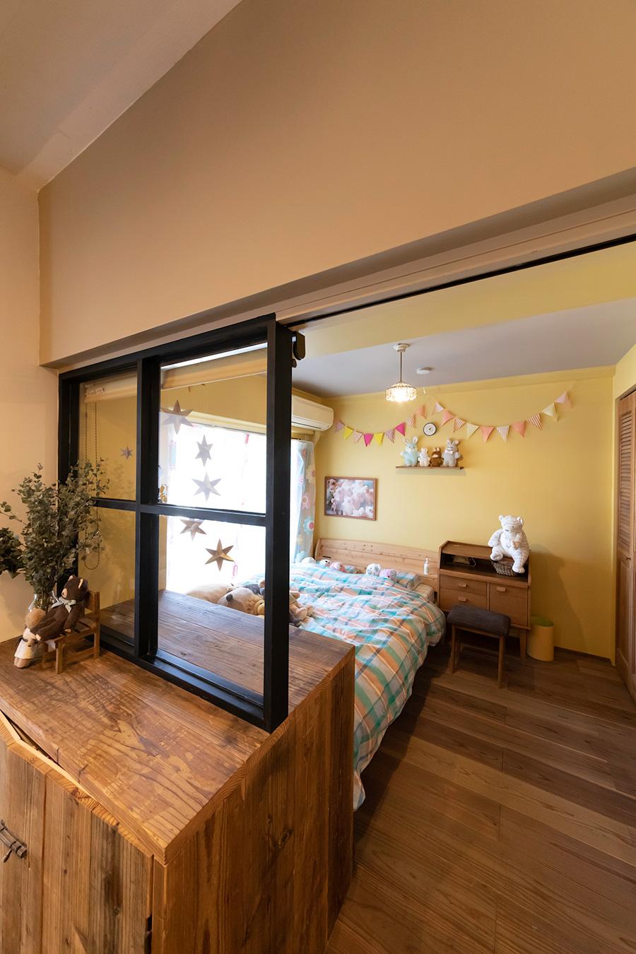 ベッドルームの壁の色はイエローに。間のガラス戸は黒にして空間を締めている。「ベッドルームの壁に棚があるといいなと思ったら、フィールドガレージさんがパッと棚を作ってくれました」