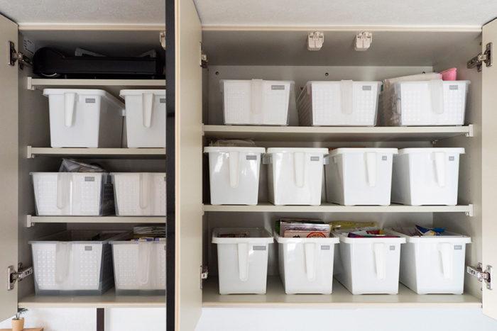 吊り戸棚の中。持ち手付きのボックスは、取り出しやすくて便利。白い紙を手前に1枚入れて、中身が見えるのを防いでいる。