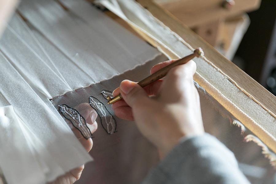 メッシュの上から極細の針を通し、下のビースをすくって縫い付けていく。独特の技法で、日本でマスターしている人は数少ないのだそう。