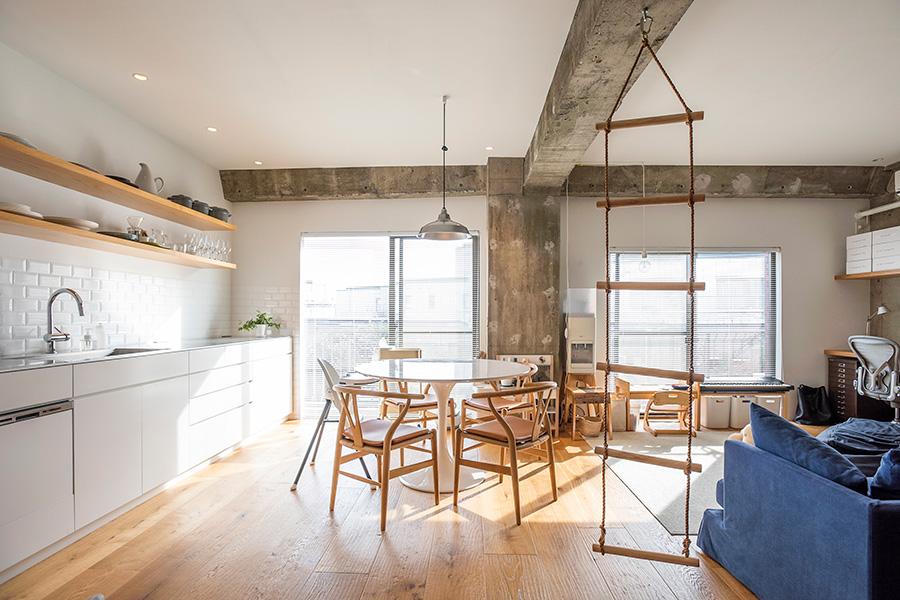 白の塗装と木の素材感に、むき出しのコンクリートをほどよくミックス。ベランダの向こうには隣のマンションの庭があり、抜けも確保されている。