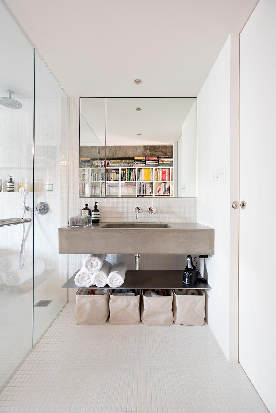 シンクはモルタル仕上げ。吊り棚などは設けないことで日常感をカバー。鏡の左端だけに隠れた収納あり。