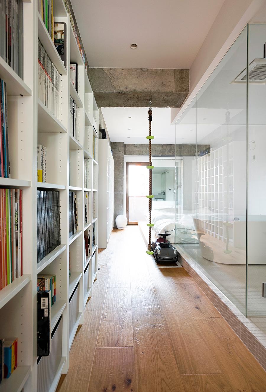 東南から北西のベランダに光が抜ける廊下には、一面にIKEAの本棚を設置。愛読書がずらりと並ぶ。