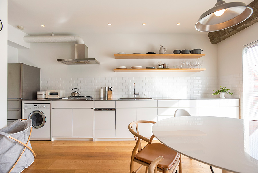 白で統一された、横幅約4.8mのキッチン。Mieleの洗濯機もここに。