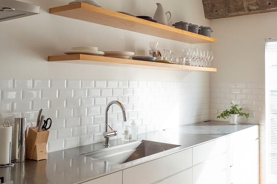 ベランダから光が差し込むキッチン。縁がカットされたタイルを使用することで陰影を生んでいる。