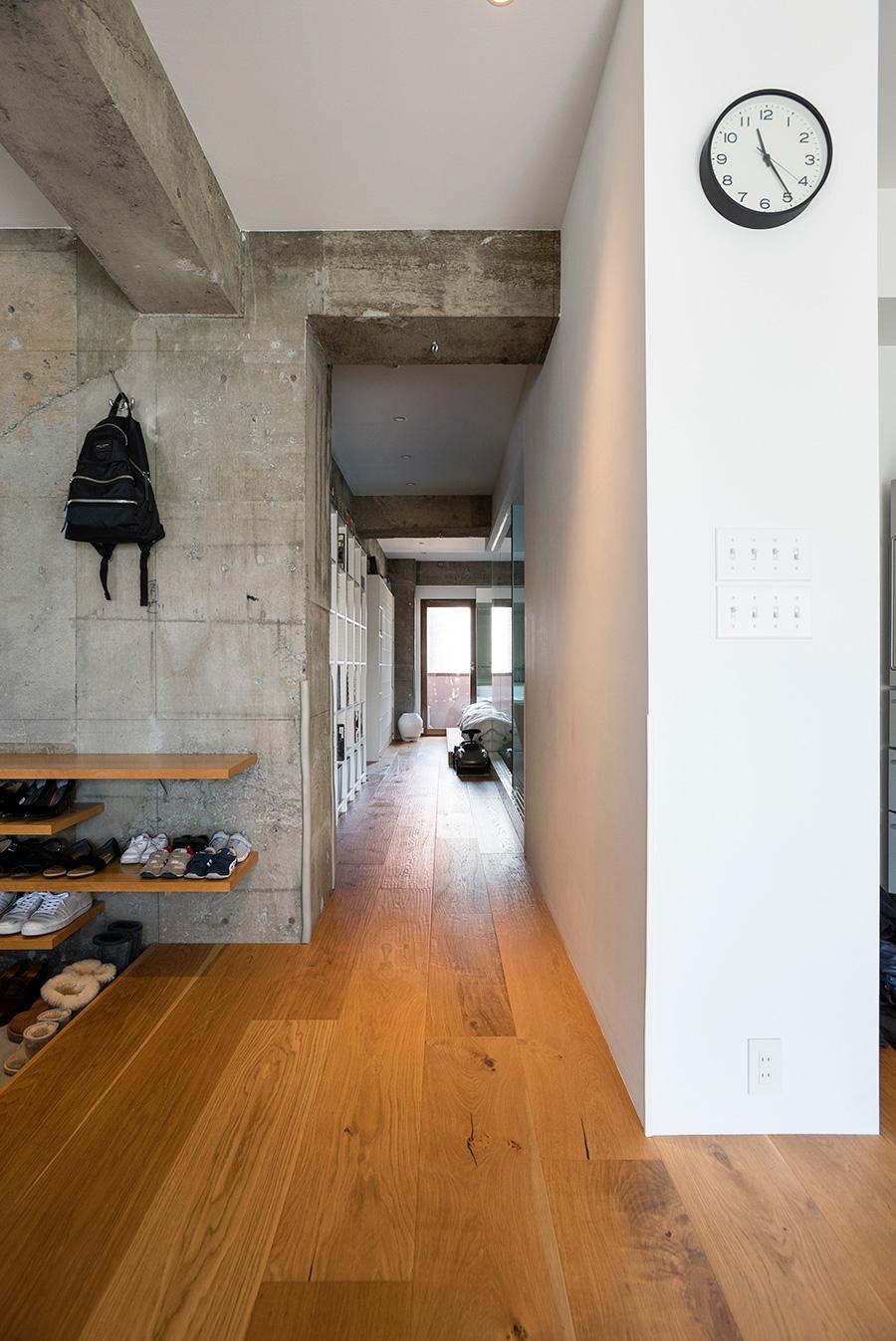幅広の、表面感のあるオークのフローリングが表情を生む。白い壁の向こうはパントリー。