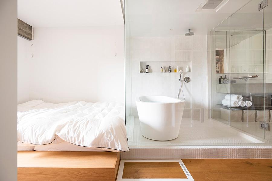 洗面、お風呂、ベッドルームがコンパクトにまとまり、動線もよい。ベッドルーム側のガラスにはロールスクリーンが取り付けられていて、目隠しすることも。バスルームの空調は天井に埋め込み、存在感を消した。