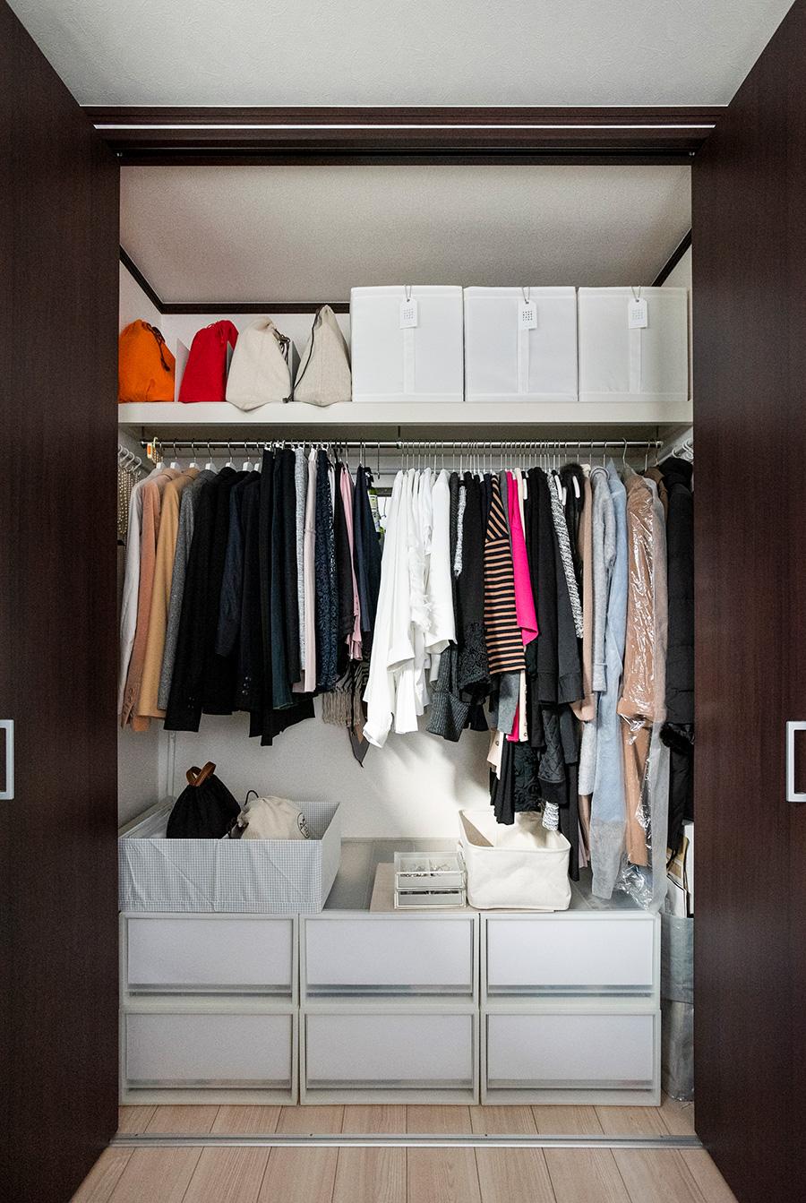 オールシーズンを通して服とバッグはここに収まるだけ。季節外のトップスのみ、タグを付けて上段の布のボックスに。カバンはブックエンドで立たせている。