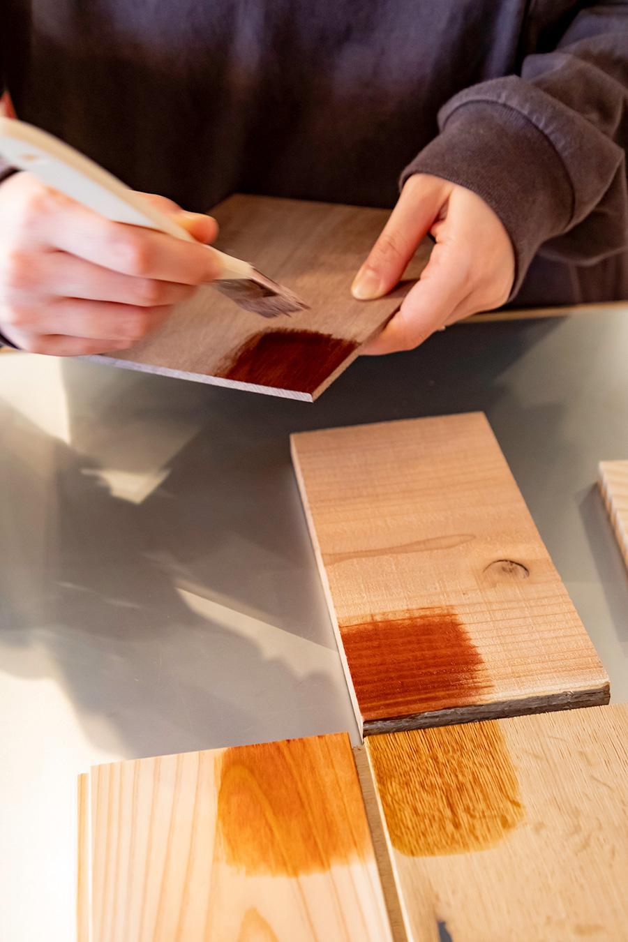 同色を塗っても木の素材によってこれだけ色に違いが出る。右手前がラスオークフローリング(オーク)、左手前が間伐材フローリング(杉)、右奥が足場板(杉)、手に持って塗っているのが壁材のスライスウッド(ウォルナット)。