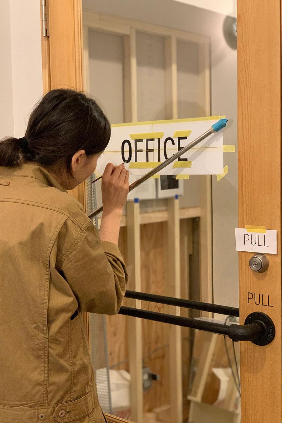 ショールームにサインペイントを施す佐古加奈子さん。『toolbox』ではサインペイントのオーダーも受け付けている。