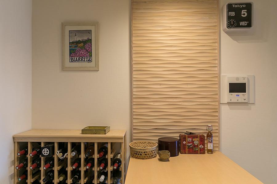 主寝室と同じ木製の壁がキッチンにも。無機質な白い壁にぬくもりを与える。左のワインラックはご主人の造作。