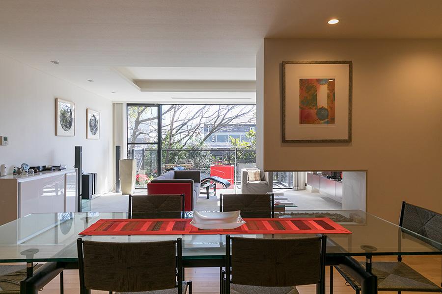 手前のリビングに置かれたル・コルビジェによるデザインのガラステーブルとカッシーナのパルディスチェア。ご主人のこだわりで設置されたライティングが壁にかけられた3枚の福本倫の銅版画を照らす。