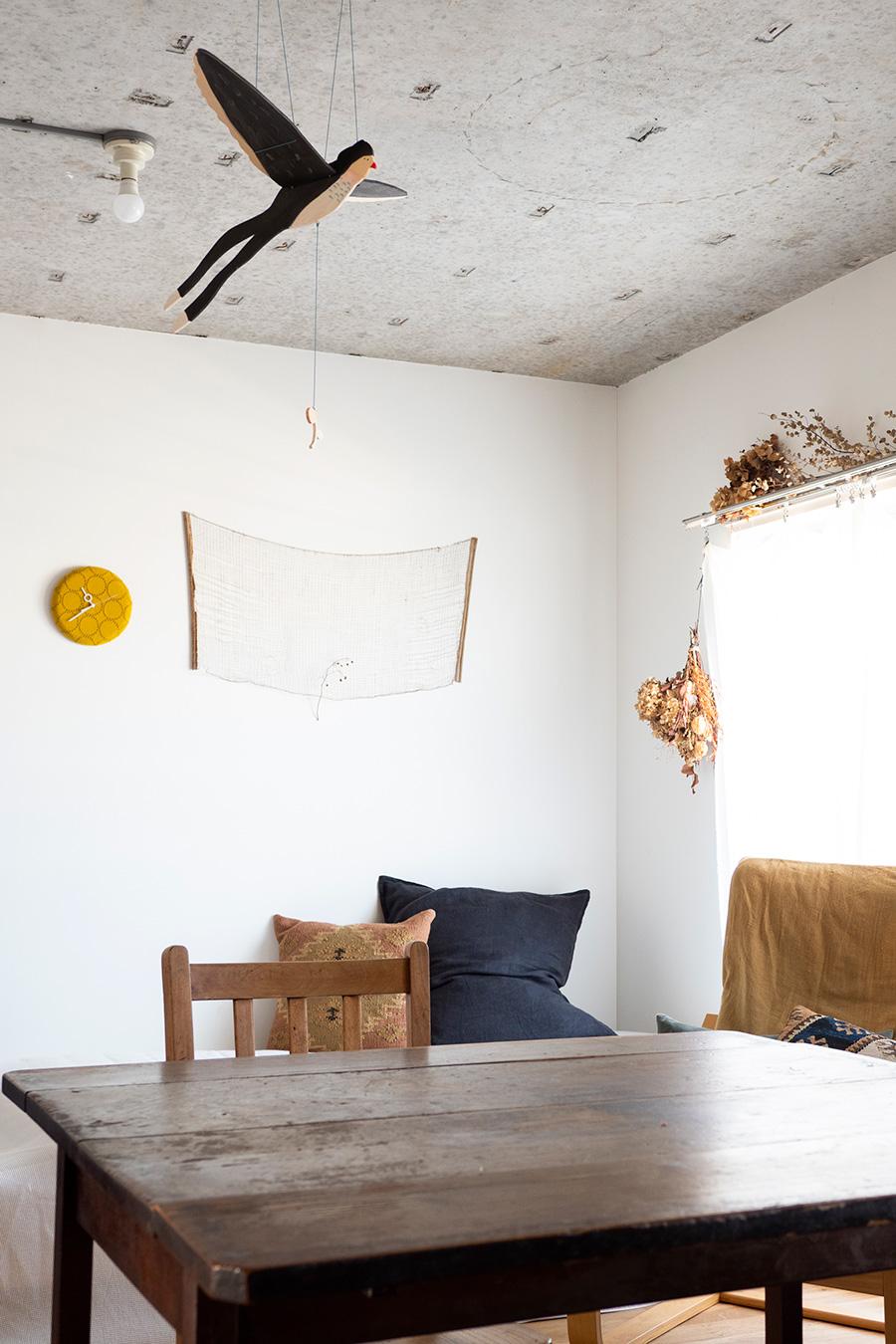 鳥のモビールは「acutti」で入荷次第売り切れる人気商品。壁には蚕網、圷さんのお母様制作の時計を。