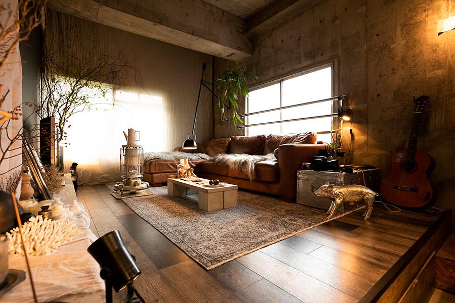 むき出しのコンクリート、木の床、壁の黒に包まれたリビング。小上がりになっていて、床下には唯一の収納スペースも。