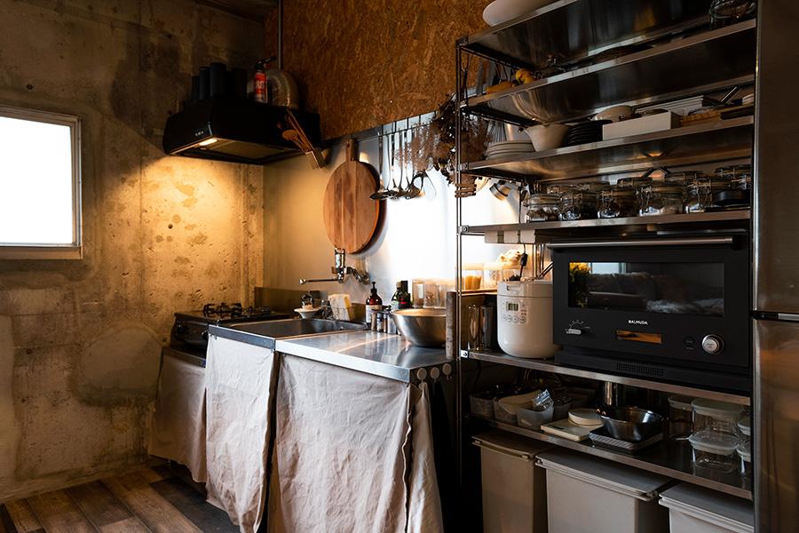 蠟引きされた帆布をキッチン台の扉の代わりに。素材感や大きさが統一された調理器具や調味料なども、整然と収納されている。