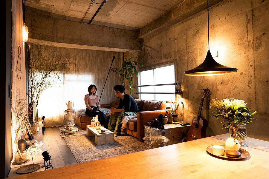 """幻想的な雰囲気のリビングで。ソファーテーブルやディスプレイしている棚は、なんとホームセンターで買ったコンクリートの盆栽棚。""""壁のコンクリートとつないでくれて、空間に統一感が出るんです""""。"""""""