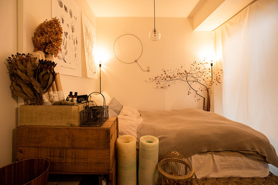 ベージュや白をベースにリネンや木、ドライフラワーなどの自然素材でまとめられた、甘さのあるベッドルーム。壁の金物のオブジェはtipura studio。