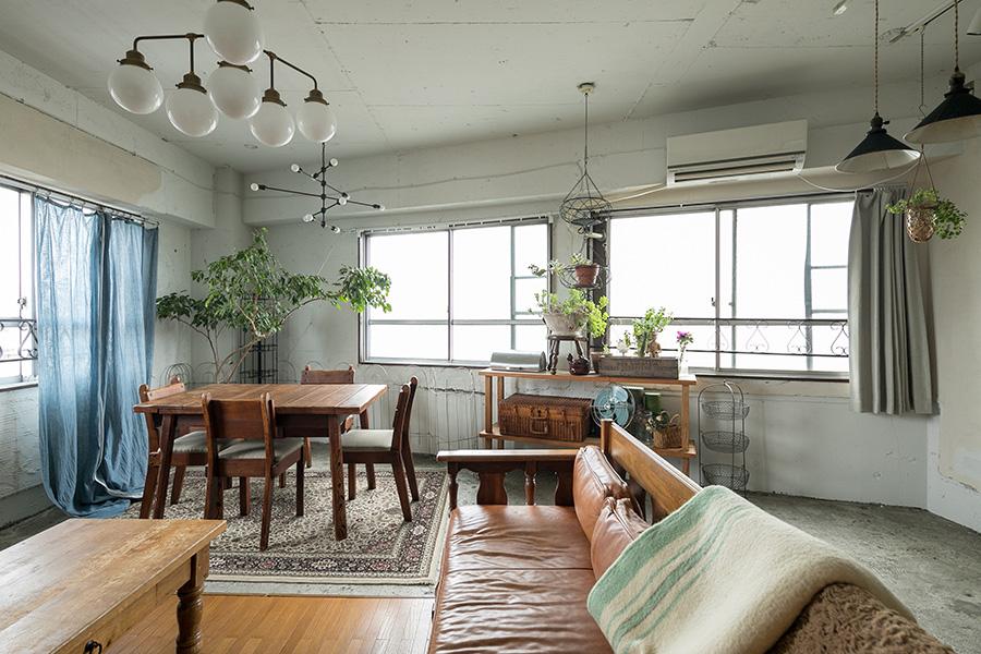 真四角ではない部屋のカタチが、奥行きとニュアンスを感じさせる。左手前のコーヒーテーブルはフランス製、奥のダイニングテーブル&チェアはアメリカのもの。レザーのソファはイギリス製。