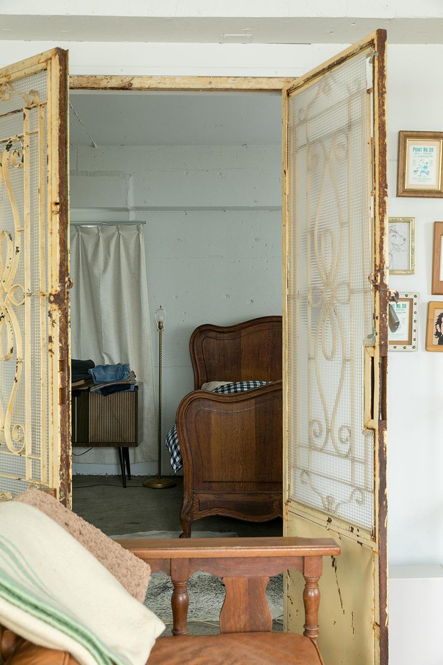 大家さんが設置してくれた扉の向こうがベッドルーム。「アメリカ製のアンティークのベッドは、日本で買えるマットレスの大きさに合わせてフレームを作り直しました」