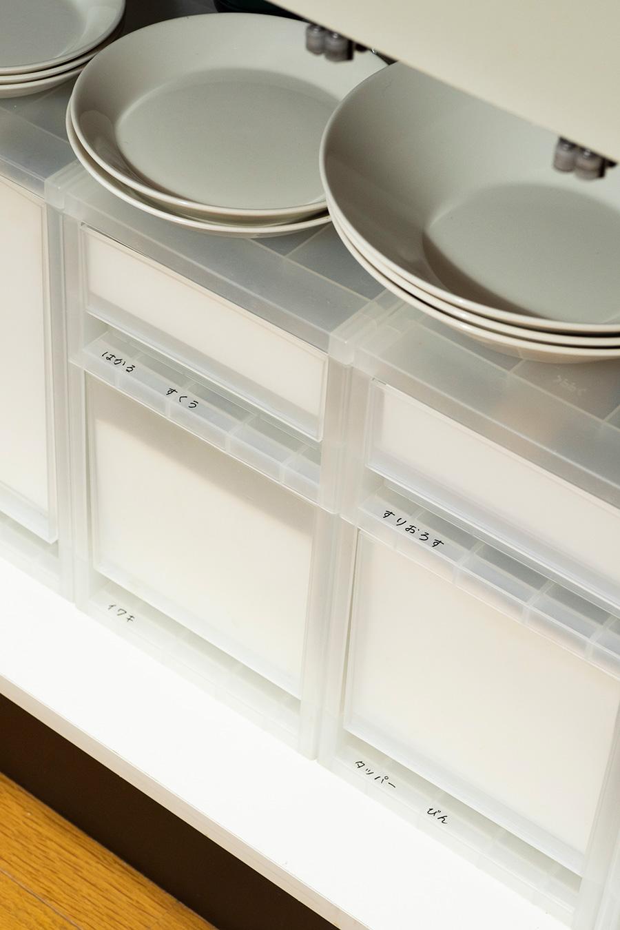 シンク下に食器置き場を設けると、取り出しやすくて便利。あまり使わない調理器具は収納ケースに。