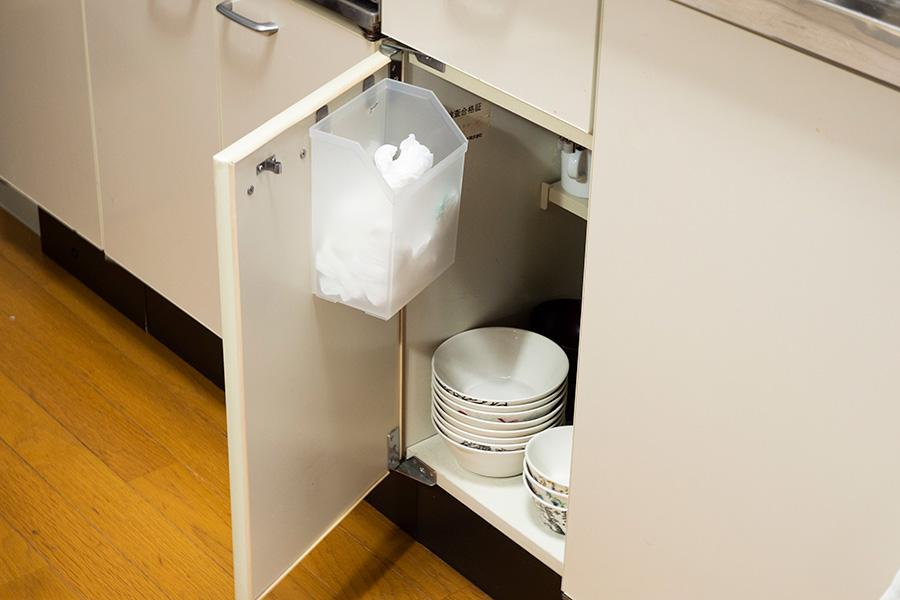 さっと取り出したいレジ袋は扉裏に取り付けたカゴに。賃貸なのであとが残らないシールが重宝。