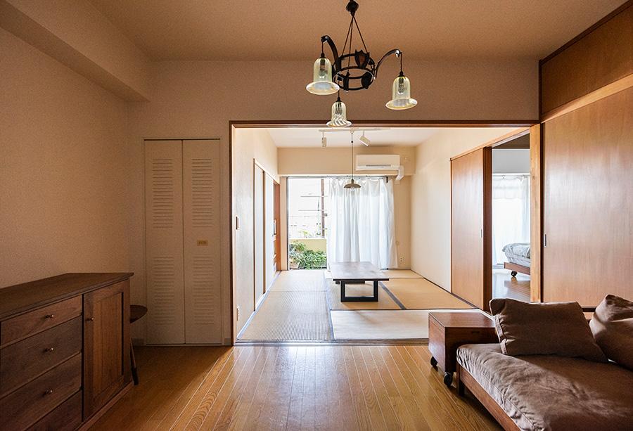 引き戸を取り払いオープンに。戸は押し入れのいちばん奥に収納。イギリスアンティークのシャンデリアに、広松木工のソファー&キャビネットが調和する。