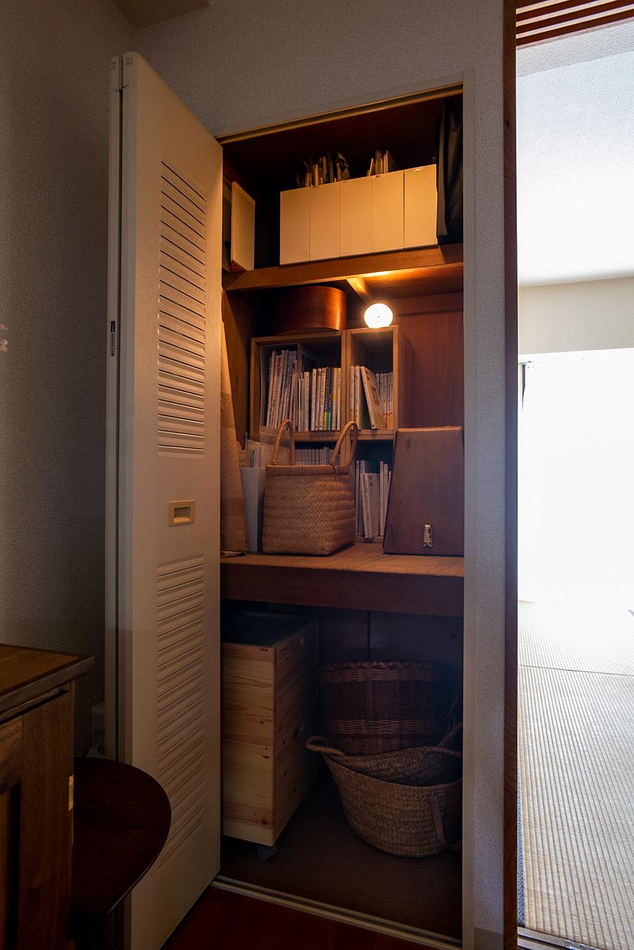 リビングの収納は開くとライトが点灯。上段に仕事関係のものを。
