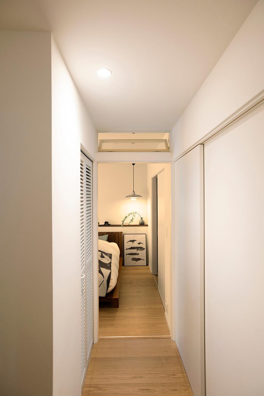廊下のダウンライトは壁に寄せてつけ、壁を照らすことで陰影を生んでいる。