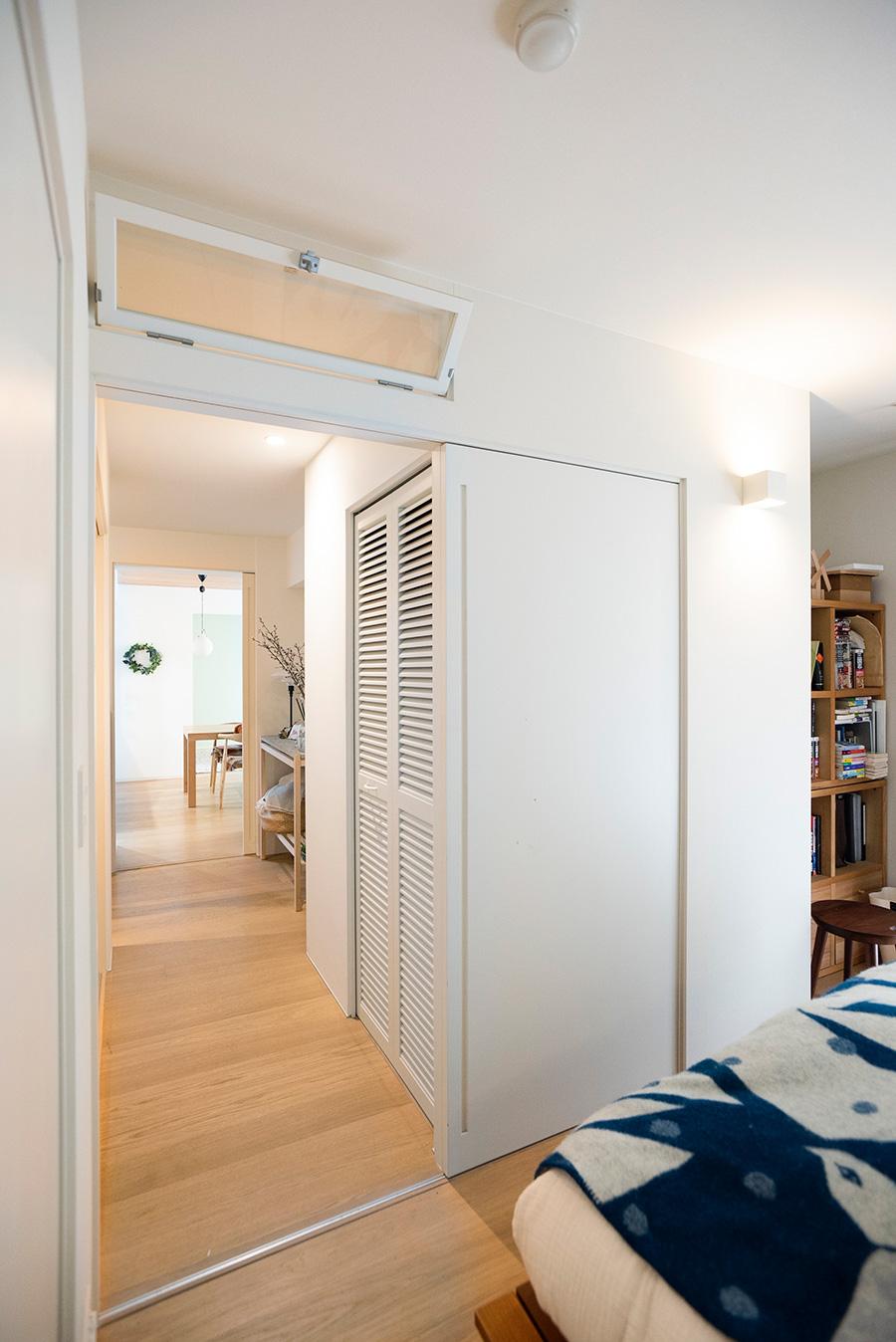 入り口に立って死角になる位置に本棚を配置。引き戸の上はガラス窓を設け、光が通るようにした。