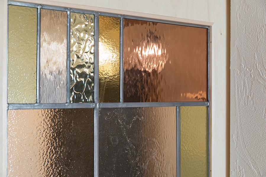 引き戸に装飾されたカラフルなステンドグラスが白い漆喰壁に映える。