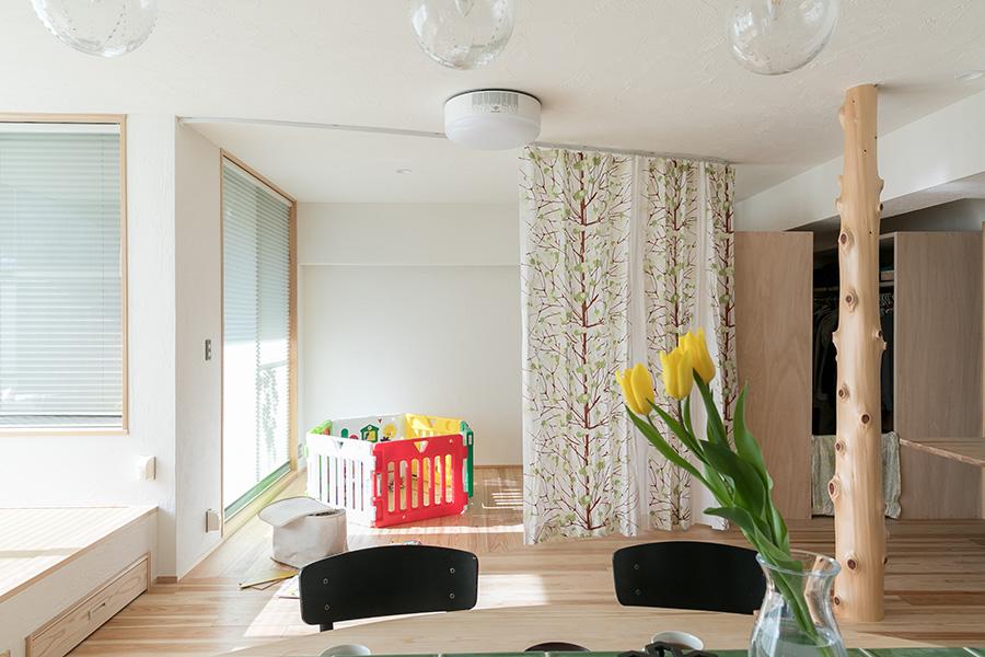 リビングの天井には、テレビのかわりに照明が一体化したプロジェクターを設置。奥の白い壁にYouTubeなどの映像を投影できる。客室としても区切れるようにとつけたカーテンは、北欧雑貨「マリメッコ」のもの。