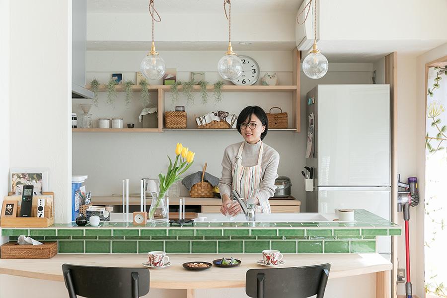 緑のタイルが印象的な可愛いキッチンカウンター。ダイニングテーブルを造り付けにすることで、さらにリビングを広く。