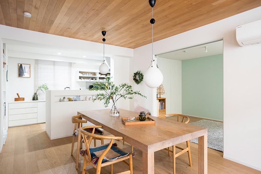 独立していたキッチンの位置を変え、オープンな対面式に。さらにまわりに梁を設けてフレームのように縁どりをした。リビング側にはニッチを設置。ダイニングテーブルは、「I+STYLERS」のもの。