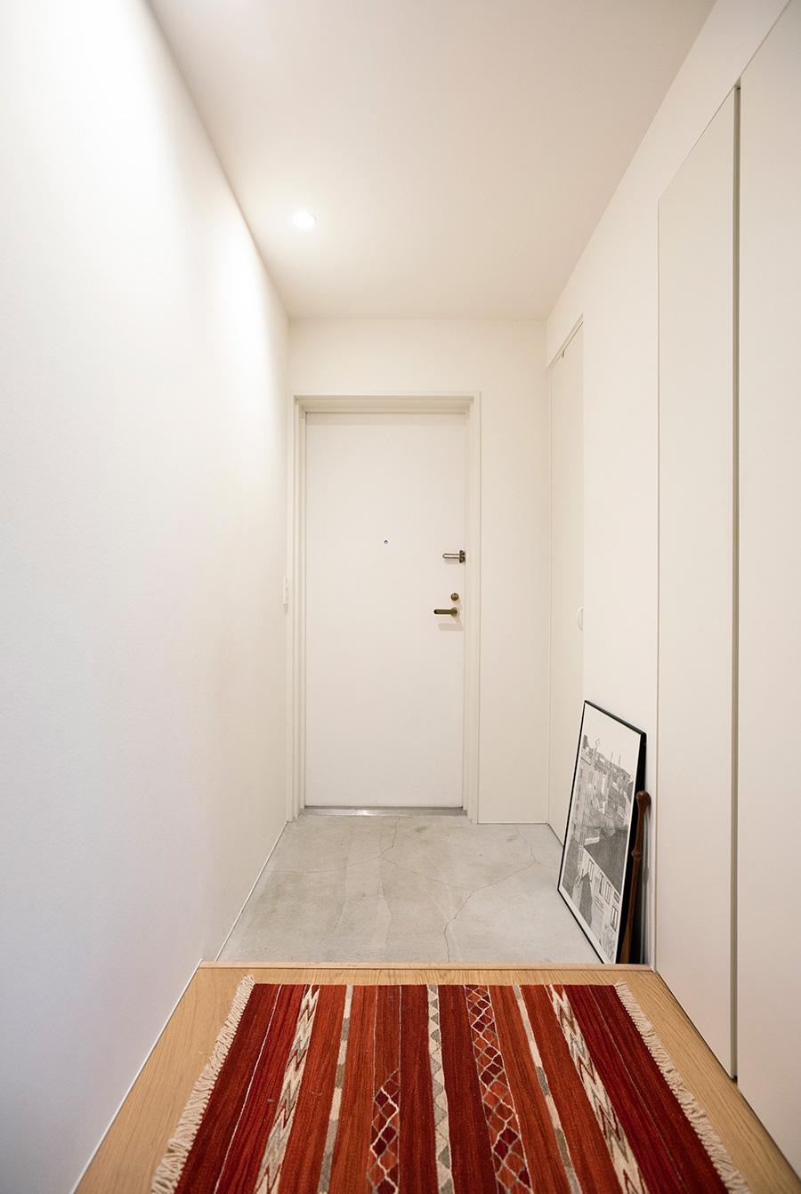 コンクリートを敷いたシンプルな玄関。共用部のため変えられなかったドアは白いシートを貼った。